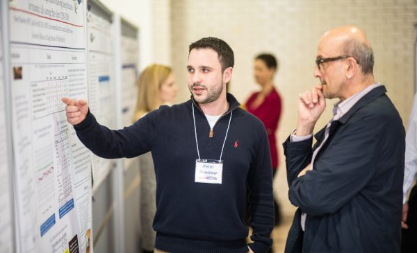 An MS student points to his research poster while explaining his research to a professor.