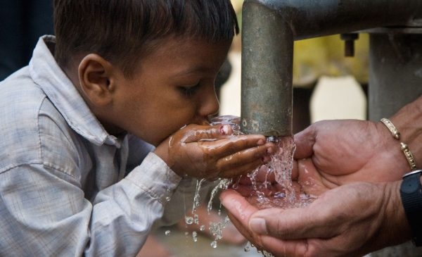 A boy drinks water from his hands, which are being filled by a pipe running with clear water.