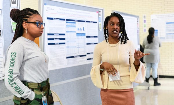 Two students present their research, standing in front of their poster, at the 2019 Research and Practice Awards day.