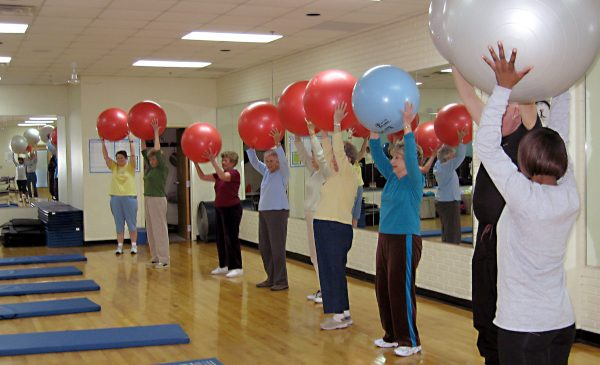 A group of seniors hold exercise balls over their head, participating in a Fit and Strong! program.