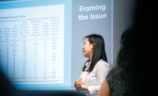 A woman discusses a series of health data figures shown on a PowerPoint, during a presentation at the 2019 Minority Health Conference.