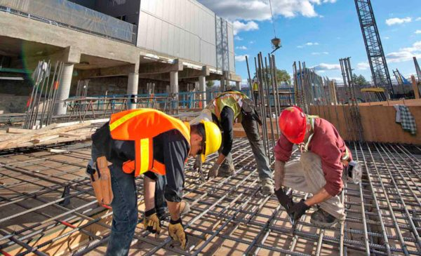 Construction workers assemble rebar and concrete at a building project.