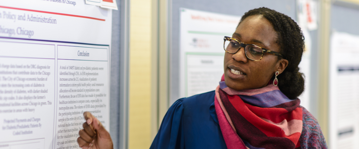 A student gestures toward her research poster while explaining the results of her research at a recent SPH Research and Awards Day.
