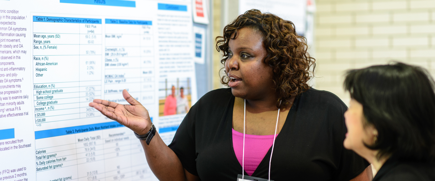 A student gestures toward her research poster as she explains her results to a staff member at Research Day.