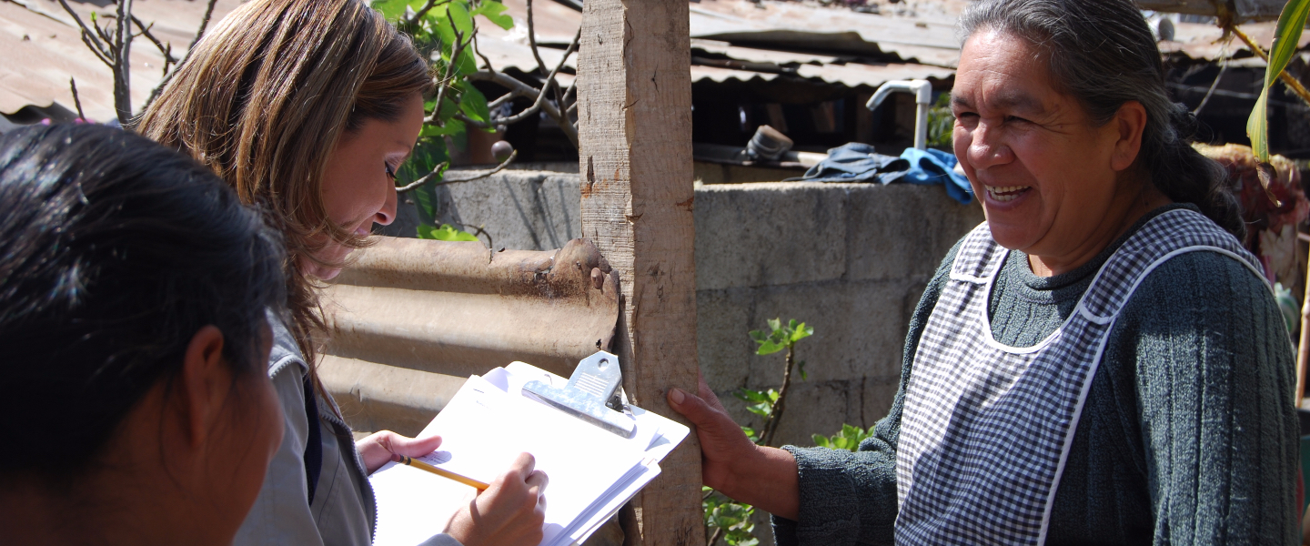 A field epidemiologist asks questions of a woman.  The epidemiologist is recording the woman's responses on a clipboard.
