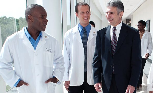 A hospital administrator at UI Health talks with two doctors as they walk down a hallway.