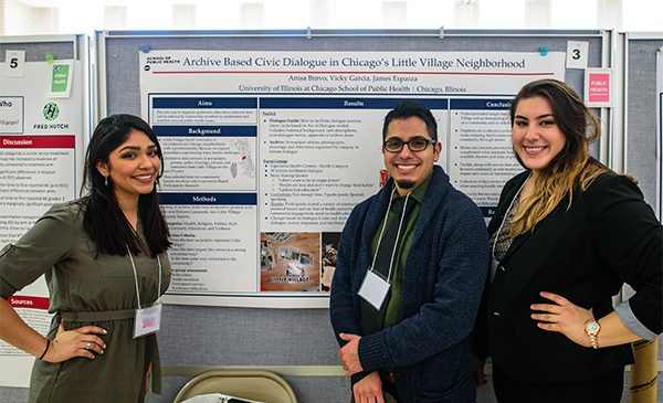 Three students pose for a picture standing in front of their research poster presentation.