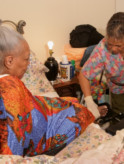An in-home care worker helps an elderly woman get dressed.