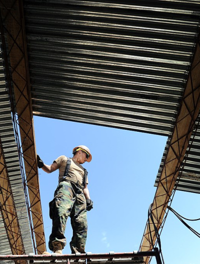 A roofer works on installing metal sheeting over a hole in a roof.