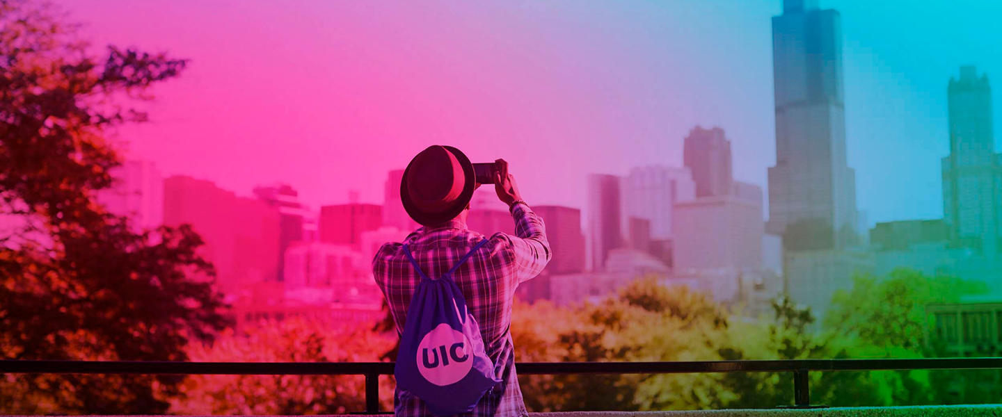A UIC student takes a photo with his phone of the Chicago skyline from atop the BSB building on UIC's east campus.