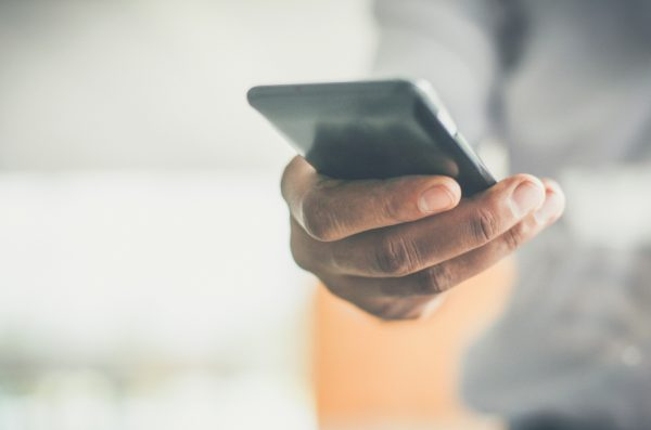 A Black man holds a phone in his hands and his scrolling through the contents on the screen.