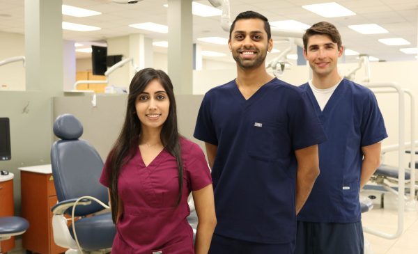 A group of students at the College of Dentistry pose for a photo in a dental suite.