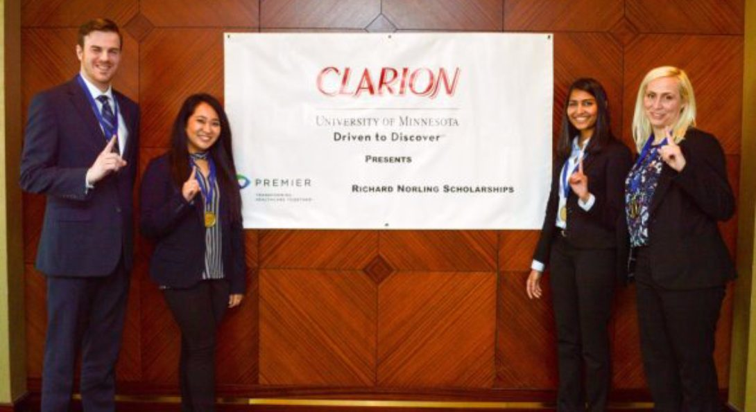 UIC students who won the Clarion Case Competition pose for a picture, holding one finger in the air signaling their victory in the competition.