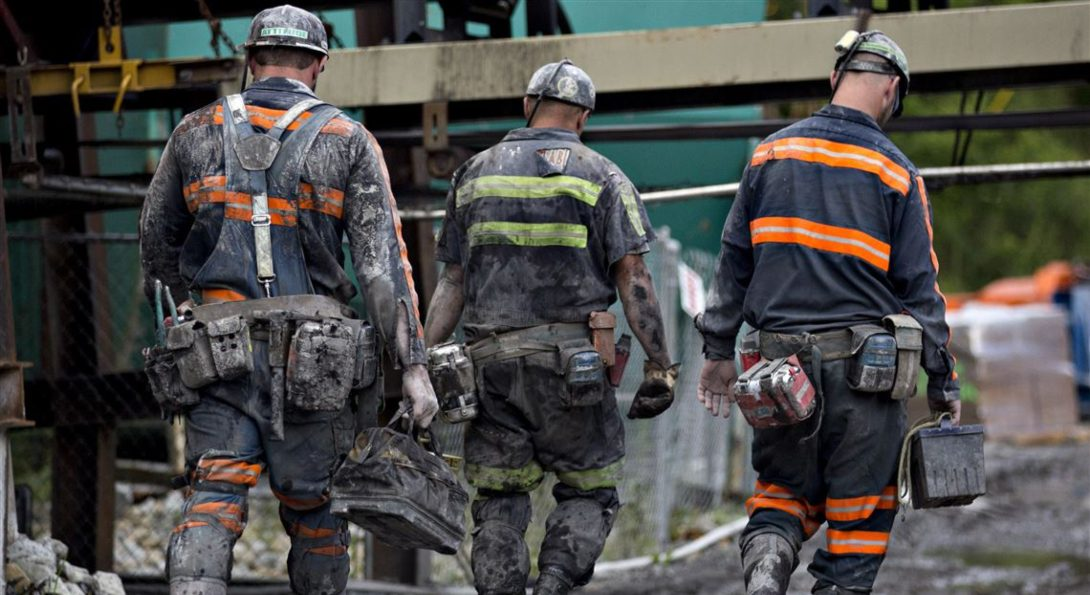 A group of coal miners walk with equipment in their hands.