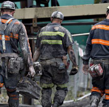 Coal miners walk together at the beginning of a shift.