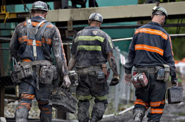 Coal miners walk together following a shift of work.