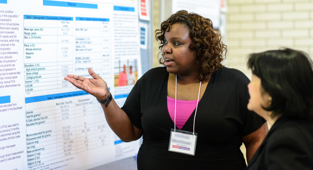 A student gestures at her poster presentation, explaining her research to an SPH staff member.