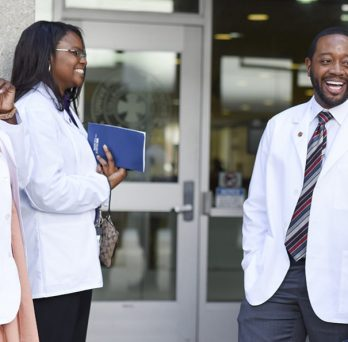 Students in the UIC Urban Health Program have a conversation standing outside a building on campus.