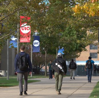 Students walk across a sidewalk on UIC's campus on a fall day, with green, red and yellow leaves on trees in the background.