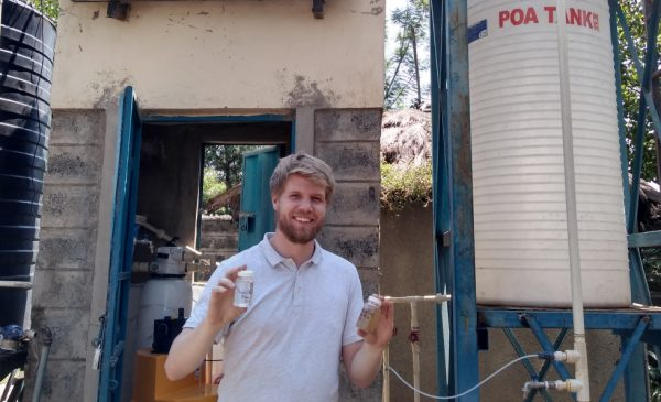 Colin Hendrickson poses for a photo holding two vials of cleaned water, standing in front of a water pumping station in Kisumu, Kenya.