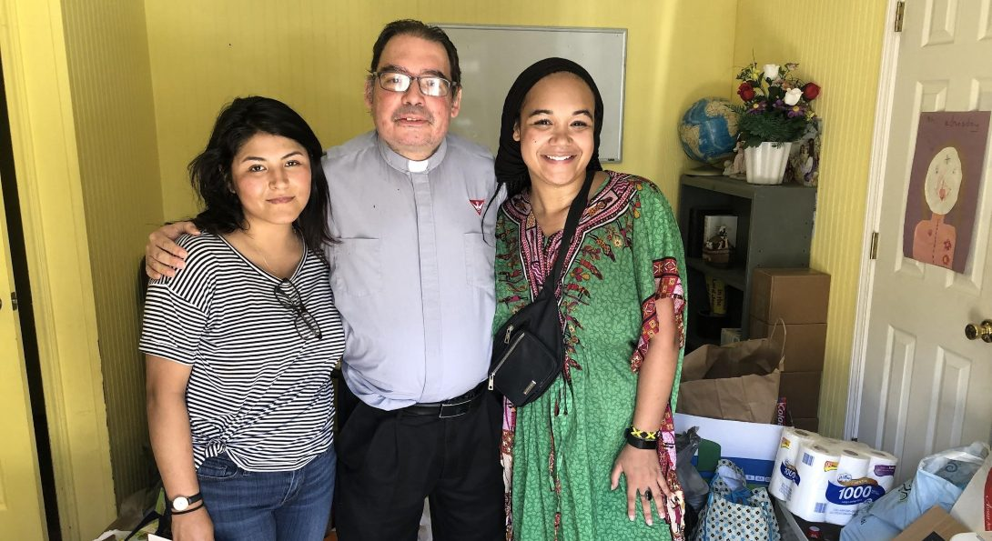 Students Kimberly Silva and Gabrielle Lodge pose for a picture with Father Roberto from St. Michael Church in Forest, Mississippi.