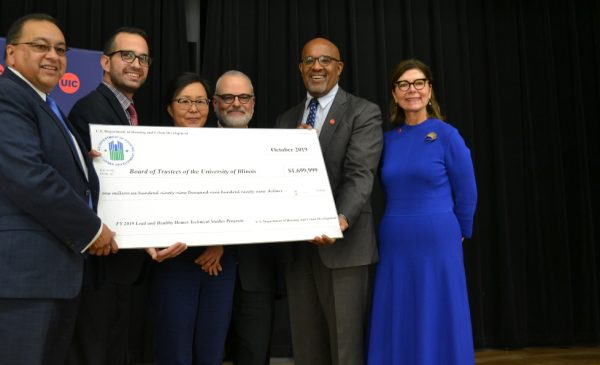 HUD Midwest Regional Administrator Joseph Galvan poses for a picture with SPH researchers and Dean Wayne Giles, holding a large cardboard check with the grant funding amount listed on it.