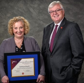 Kathryn Roach poses for a photo with Chancellor Michael Amiridis.  Kathryn is holding her award plaque.