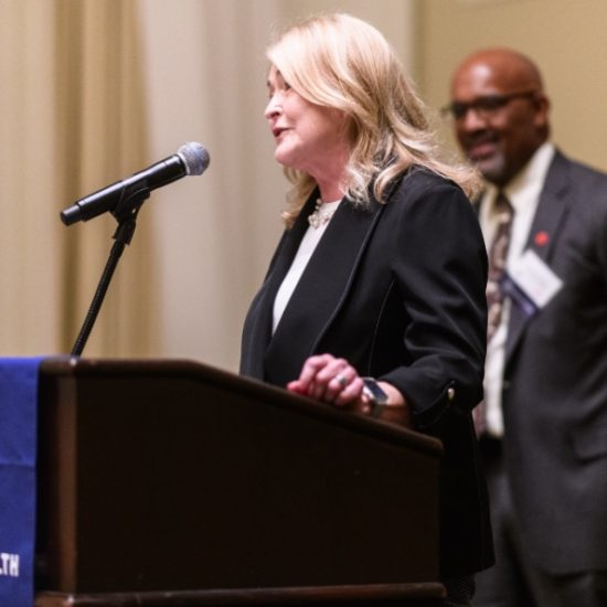 Denise Oleske speaks at a podium, with dean Wayne Giles in the background, at the School of Public Health's 50th anniversary kick-off event in October 2019.