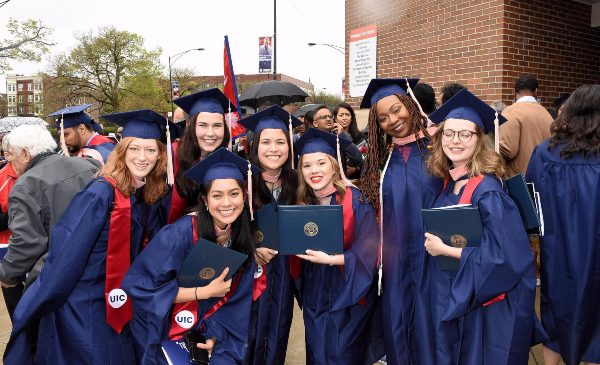 Graduates pose for a group picture outside the Credit Union 1 Pavilion following the 2019 Commencement ceremony.