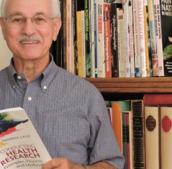 Fred Kviz stands in front of a bookshelf, with a book in hand, posing for a picture.