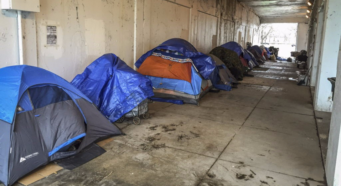 A group of tents lined up under an overpass in Chicago, presumably the temporary place of living for homeless residents of the city.