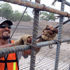 A construction worker uses a metal tool to tighten bars on a metal frame.