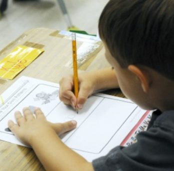 A student works on an assignment n patterns, writing with a pencil on paper, while sitting at a desk in a Chicago Public School.