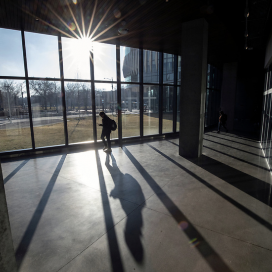 A student walks through a UIC campus building, with the sun shining through the window.