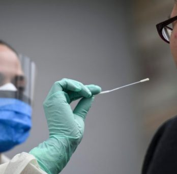 A medical professional administers a COVID-19 nasal swab test.