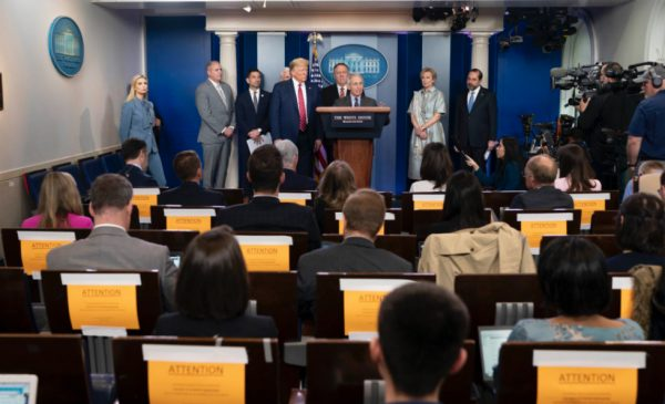 Media practicing social distancing listen during a press conference at the White House.