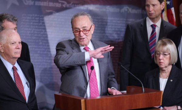Senator Chuck Schumer speaks with Congressional colleagues while addressing the media on the details of a paid sick leave bill.