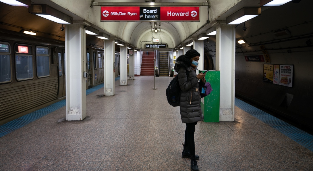 A solitary rider wears a mask while waiting for a CTA train at an underground station in Chicago.