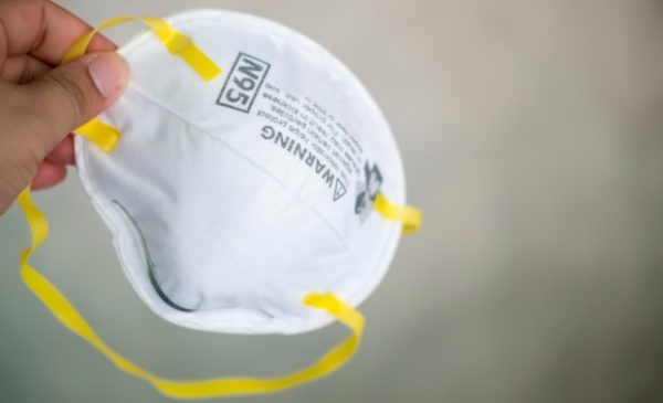 A person holds an N95 respirator mask in their hand.