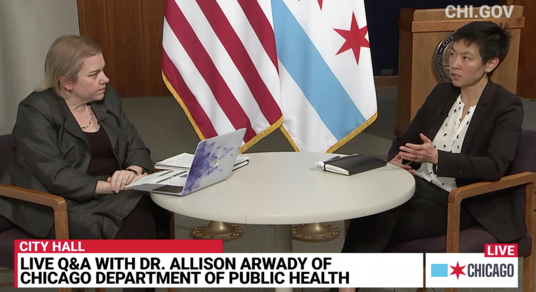A screenshot of the video broadcast of the Chicago Department of Public Health's daily COVID-19 update, with Dr. Allison Arwady and SPH's Dr. Janet Lin seated at a table discussing issues related to the outbreak.