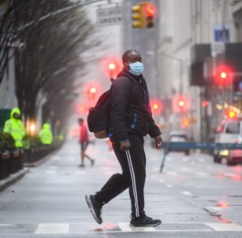 A person wearing a mask walks across a street intersection.