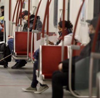 Subway riders in Toronto wear facemasks during their commute.