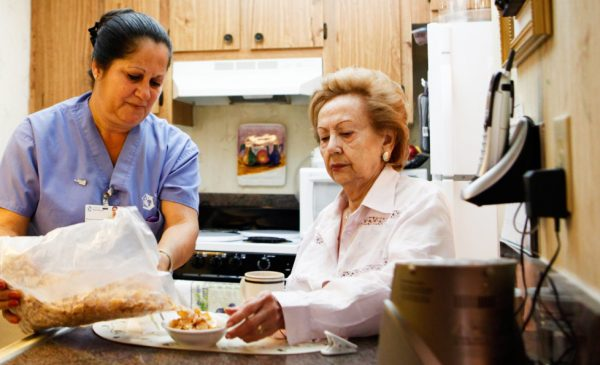 A home care aide prepares breakfast for an elderly woman in the woman's kitchen.