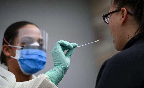 A medical professional prepares to perform a nasal swab COVID-19 test with a patient.