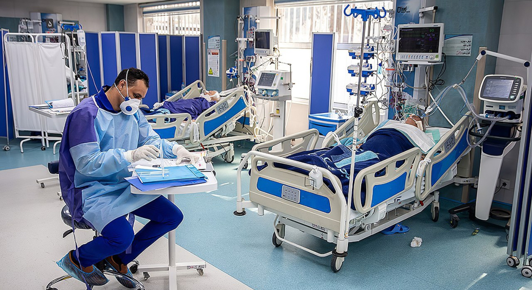 A doctor monitors the condition of two COVID-19 patients using ventilators.