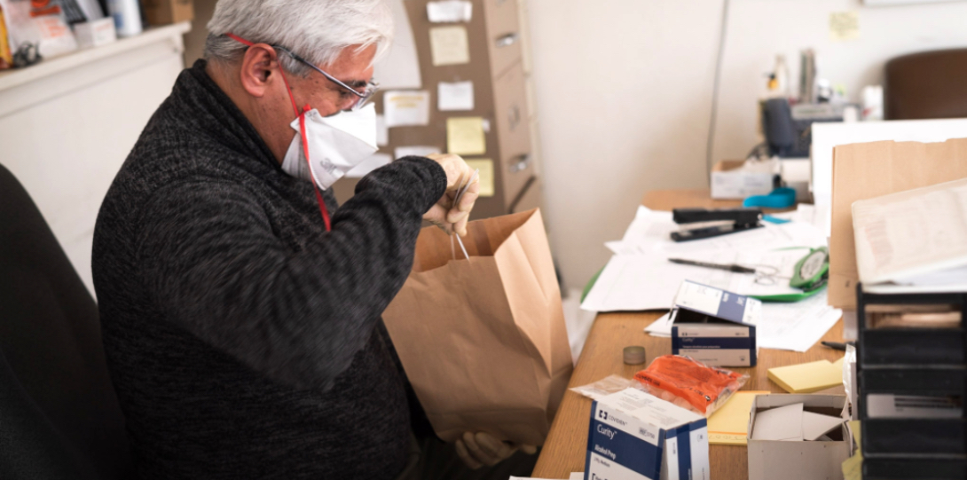 Antonio Jimenez, director of SPH's Community Outreach Intervention Projects, prepares a bag of clean needles and other supplies for clients.