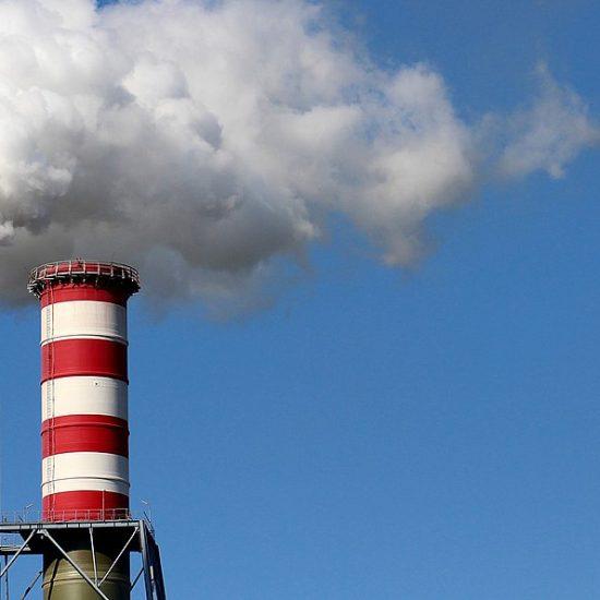 Two smokestacks emit a large cloud of white smoke.