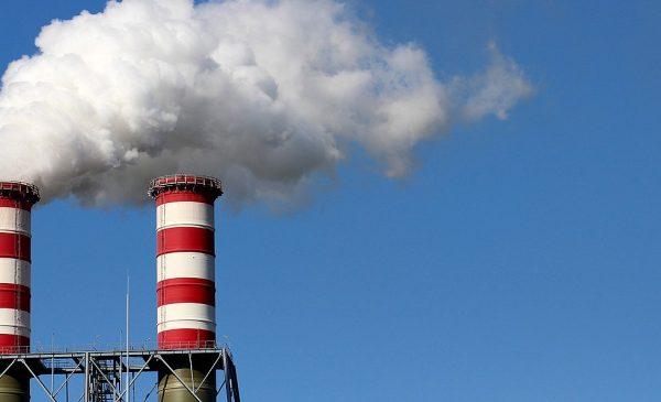 Two smokestacks emit white clouds of exhaust.