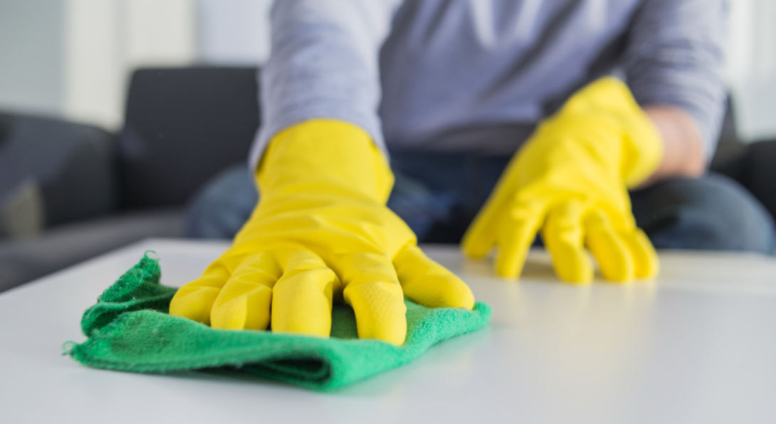 A person disinfects a table in their home with a green rag, while wearing yellow protective rubber gloves.
