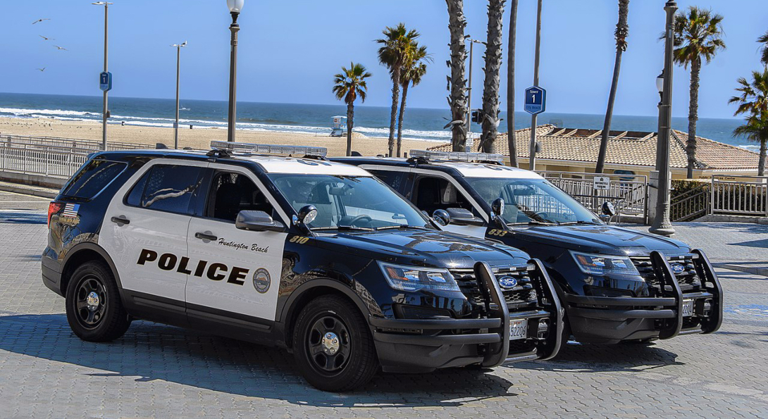 Two Huntington Beach police cars are parked near a beach, where police are monitoring beach closures during the COVID-19 pandemic.